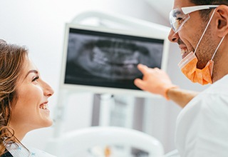 Patient and dentist looking at digital x-rays